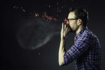 Image shows a man blowing up a balloon.