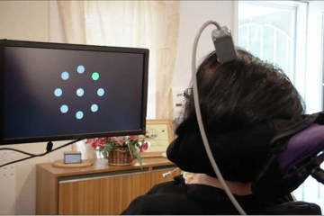 Image shows a woman using the bci to move a cursor.