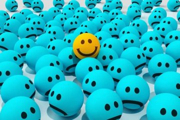 Image shows a smiley yellow ball among sad blue balls.