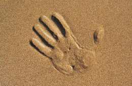 Image shows a hand print in sand.
