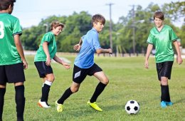 Image shows kids playing soccer.