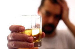 Image shows a man drinking whiskey.