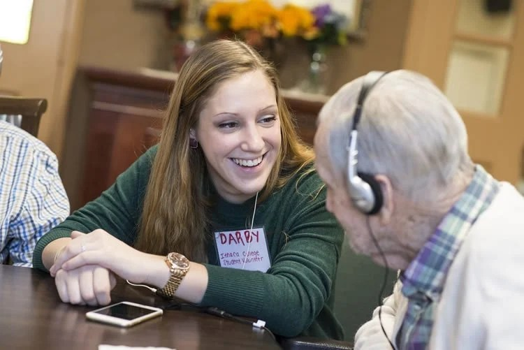 Image shows a volunteer playing music for an alzheimer's patient.