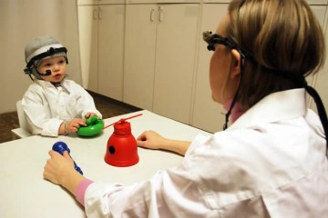 Image shows a little boy with a cochlear implant.