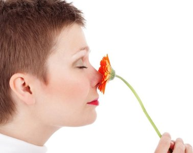 Image shows a woman smelling a flower.