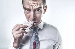Image shows a man eating a cookie.