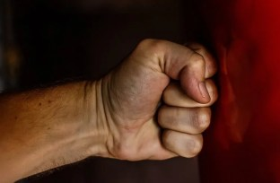 Image shows a fist hitting a wall.