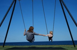 Image shows kids on a swing.