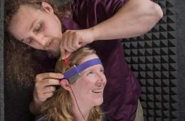 Image shows the researcher putting the tDCS machine on a subject's head.