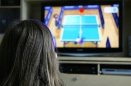 Image shows a child playing a tennis video game.