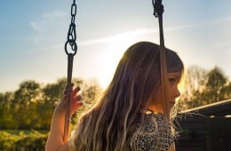 Image shows a lonely lookin little girl on a swing.