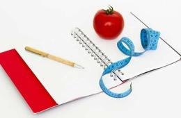 Image shows a tomato, a note book and a tape measure.