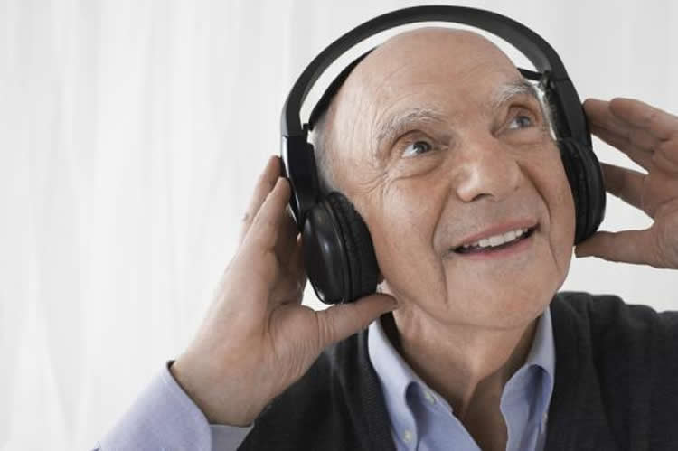 Image shows an old man listening to headphones.