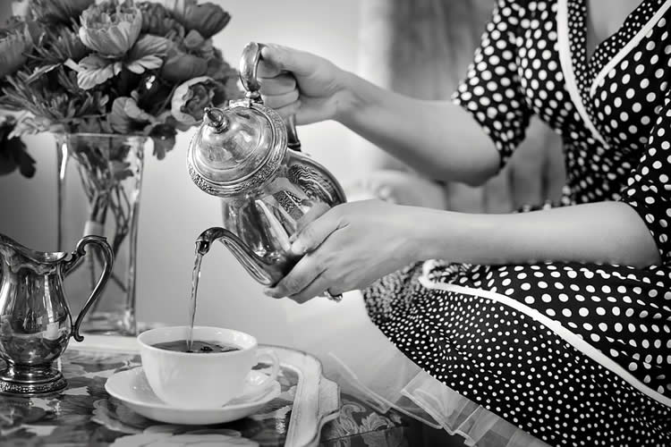 Image shows a woman pouring tea.