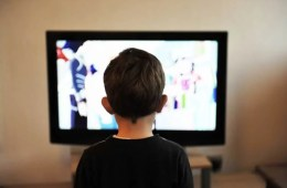 Image shows a boy watching TV.