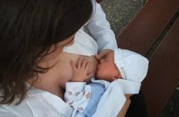 Image shows a woman breastfeeding a newborn.