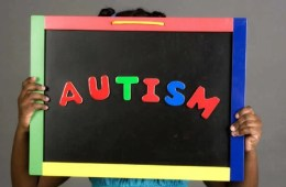 Image shows a girl holding up a sign with the word Autsim on it.
