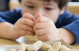 Image shows a child looking at peanuts.