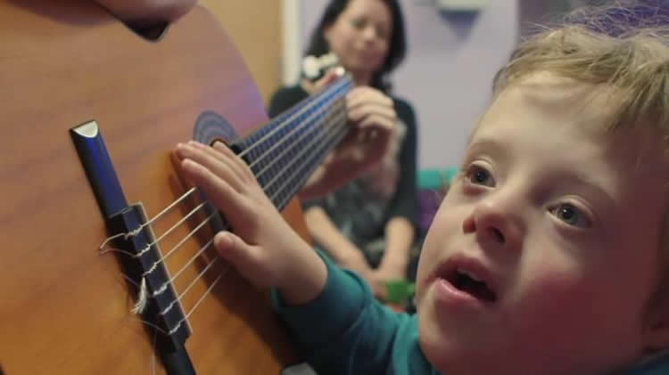 Image shows a little boy playing a guitar.