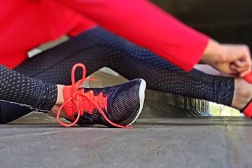 Image shows a person lacing up running shoes.