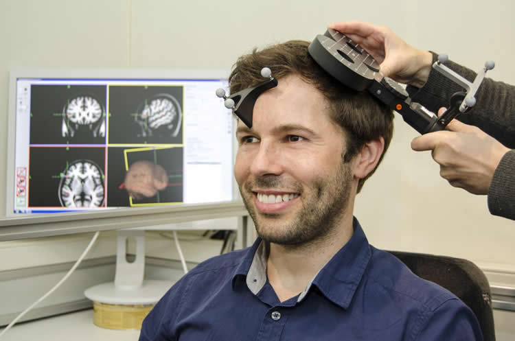 Image shows a person with a TMS machine.
