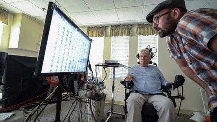 Image shows the researcher and participant in a wheel chair.
