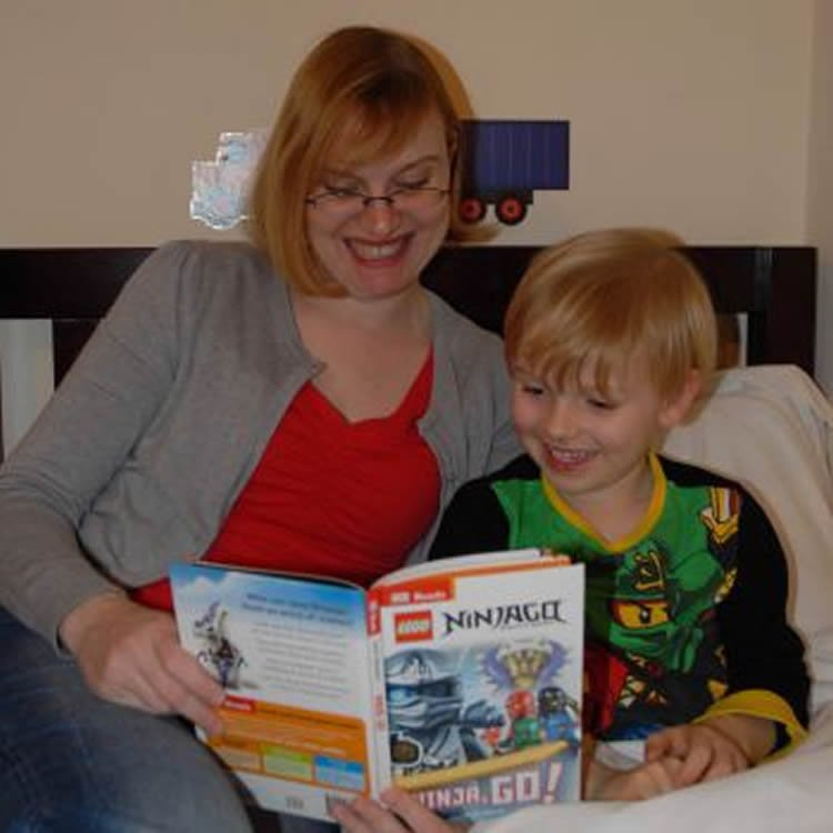 Image shows a mom and child reading.