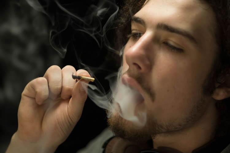 Image shows a person smoking.