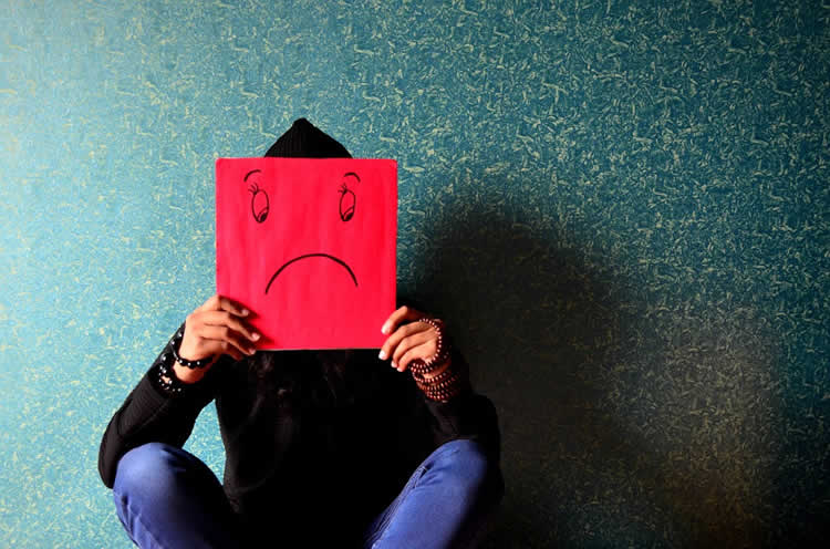 Image shows person holing up a sad face sign.