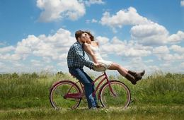 Image shows a couple on a bike.