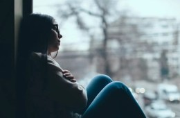 Image shows a preteen girl sitting next to a window.