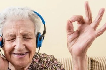 Image shows an old lady listening to music.