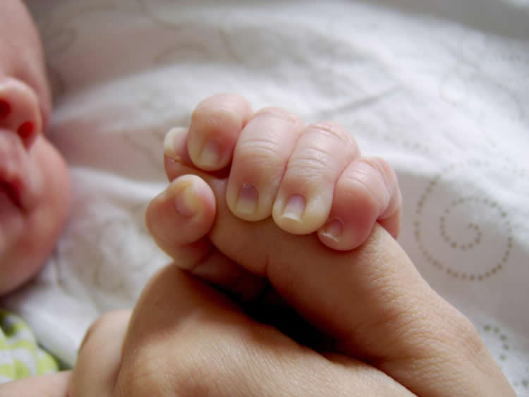 This image shows a baby holding its parent's thumb.