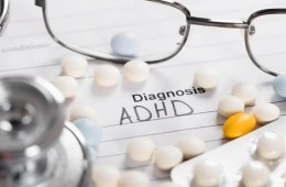 """Image shows a pills and paper with """"Diagnosis: ADHD"""" written on it."""
