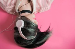 Image shows a girl listening to music on headphones while laying down.