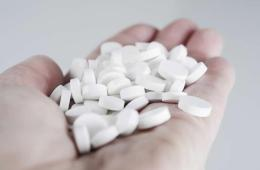 Image shows hand full of pills.