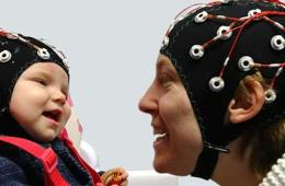 a baby and parent in eeg caps