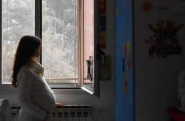 a pregnant woman is looking through a window in this image.
