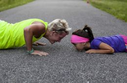 Image shows a woman and child doing push ups.