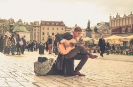 a woman playing a guitar on the street