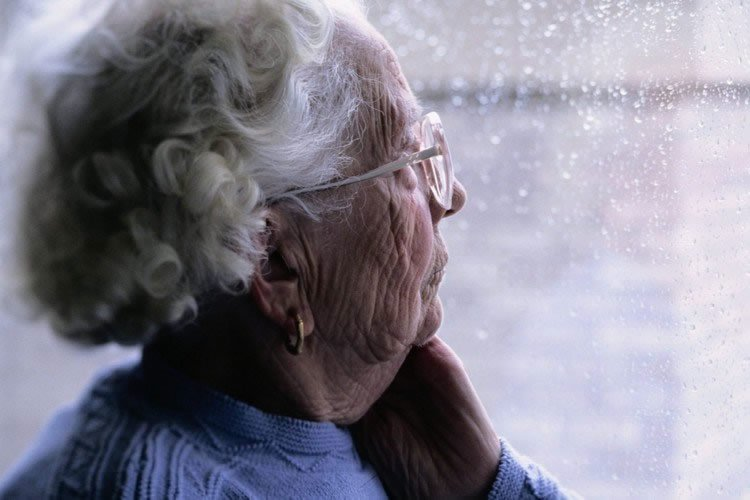 an old lady looking out of a window at the rain