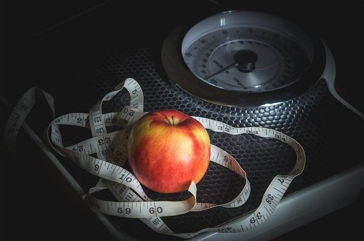 a scale, tape and apple