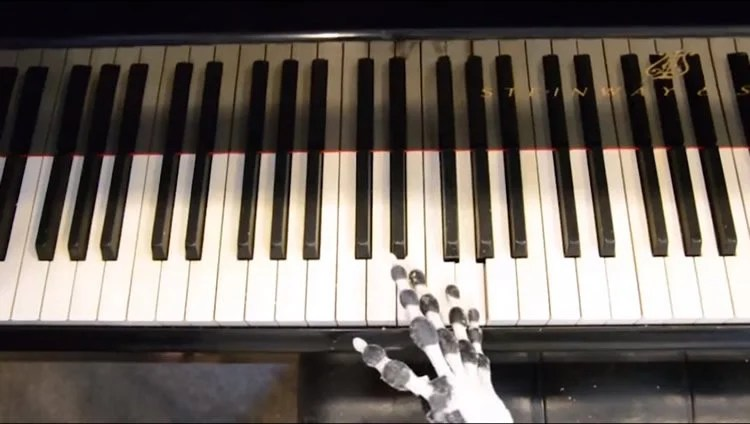the robotic hand playing a piano