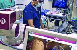 Two surgeons are shown in an operating room with a monitor in the foreground.