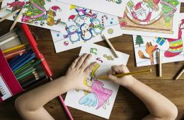 This shows the hands of a child coloring in a picture
