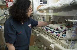 This shows the lead research looking after a baby in a neonatal ward