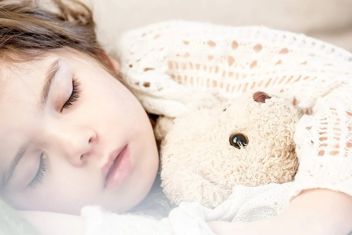 This shows a child sleeping with a teddy bear