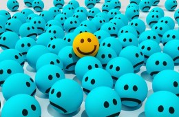 This shows a happy face painted on a ball surrounded by unhappy faced balls