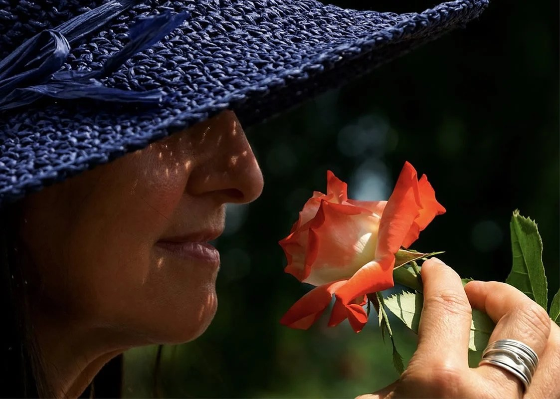 This shows a woman smelling a rose