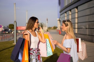 This shows two women with shopping bags